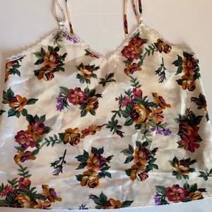 Vintage, äldre H&M linne i satin. Stl L, funkar på S-M bäst, men se mått! Mått (mätt platt): byst/armhåla-till-armhåla 46,5 cm, vidd nertill 52 cm och längd fr axel ca 50 cm (reglerbara axelband) Frakt 44kr.