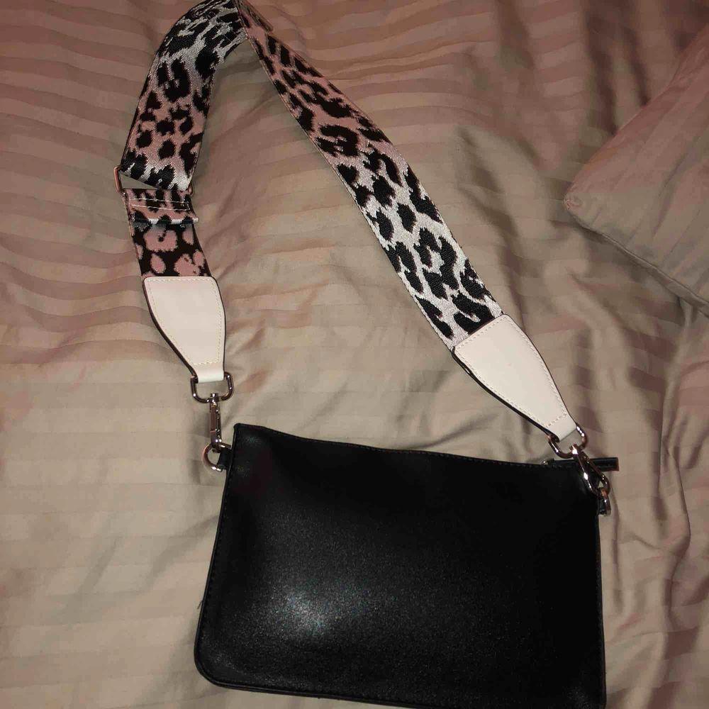En svart väska med leopard band. Inte använt. Skriv om du är intresserad! Frakt ingår ej i priset.. Accessoarer.