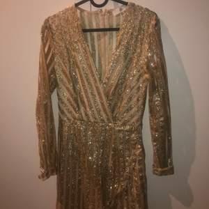 Guldiga glittrig klänning som är köpt på nelly.com.      Använd 1 gång. Perfekt nyårs klänning eller för finare tillfällen! Frakt tillkommer.