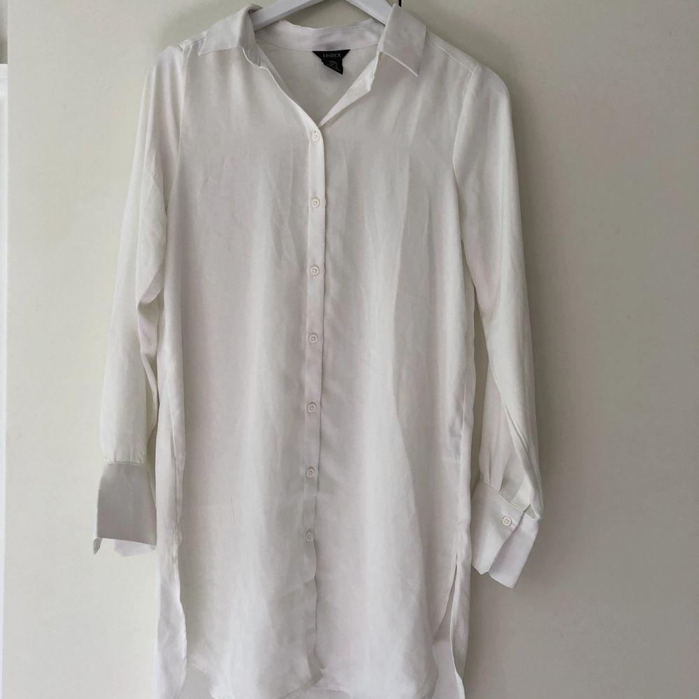 Vit, lite längre skjorta från Lindex. Endast använd en gång. Köparen står för frakten.. Skjortor.