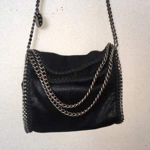 Svart Stella McCartney inspirerad väska med grå/silvrig kedja. Är knappt använd så den är i nyskick. (Säljer pgr har för många väskor.). Kan mötas upp i Stockholm annars står köparen för frakten.⭐️
