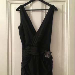 Säljer en LBD, snygg draperad svart klänning från Dry Lake med V-öppning framtill och i ryggen. Oanvänd, prislapparna/tagsen kvar. Dragkedja i sidan. Nypris 500kr.