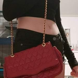 Gullig röd handväska med hjärtan på. Det går att ha väskan på olika sätt då banden är justerbara. Insidan av väskan är leopard mönster. Den här även gulddetaljer. Den är i okej skick