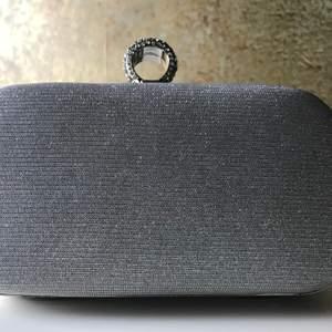 Round clutch med silverdetaljer. Avtagbar axelrem i silverkedja.