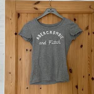 Grå T-shirt från Abercrombie i strl XS. Köpt för några år sedan. Har ett litet hål som går att sy igen på framsidan (bild 3) annars väldigt bra skick. Pris kan diskuteras.