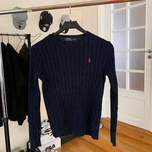 Marinblå kabelstickad från Ralph Lauren med rött märke. Fint skick - använd några gånger. Köparen står för frakten!