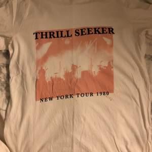 Vit t-shirt med rosa tryck i strl XS. En liten fläck under trycker, säljs därför billigt. Skriv om du vill ha bättre bilder på plagget, tex passform på kroppen osv!