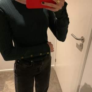 Fin mörkgrön tröja från bershka med guldiga detaljer.