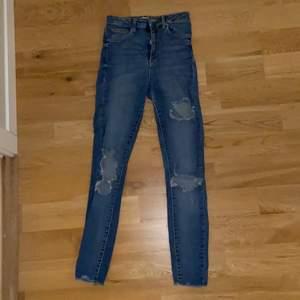 Blå jeans med slitningar på framsidan. Väl använda men i bra skick. Jeansen är tighta och mycket bekväma med hög midja. Var favoritjeansen väldigt länge.