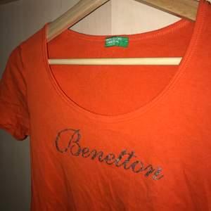 jättefin orange benetton T-shirt köpt second hand. Den har silvrigt tryck på framsidan och är i storlek Xs-S beroende hur man vill den ska sitta. Kan mötas upp eller står köparen för frakten.