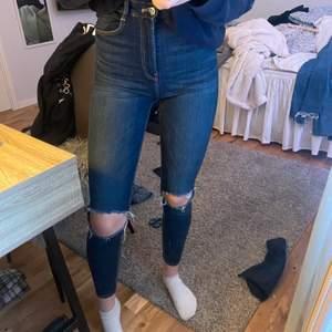Ett par mörkblå tighta jeans med hål på knäna, säljer då jag har för mycket jeans och vill bli av med de! Frakt står köparen för!