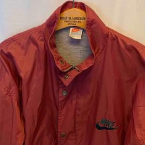 Vintage Nike Crimson Nylon Bowerman Coach Jacket. Jackan är i mycket gott skick, Storlek S men det är baggy fit / oversized   Kan hämtas i Uppsala eller skickas mot fraktkostnad.