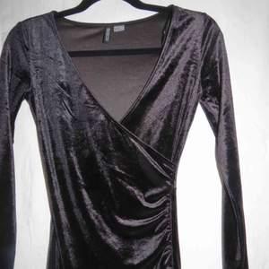 Klänning i svart sammet, den går omlott och är kort ! Väldigt fint skick , endast använd 1 gång :D