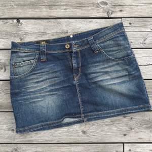 """Väldigt lågmidjade (sitter på höften), kort jeanskjol från märket Lee. Lite """"vintage"""" style. Storlek XL men skulle säga att den är mer som en L. Ganska stor i midjan på mig som har M. Fint skick! Frakt: 28kr"""