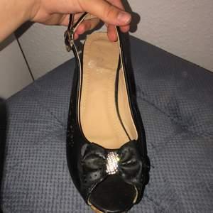 Svarta sommar klackar med rosett och diamanter, en sko är missfärgad som man kan se på sista bilden men syns ej när man har på sig,  och har lite små skrapor på klacken som jag kan skicka bild på ifall ni vill se.