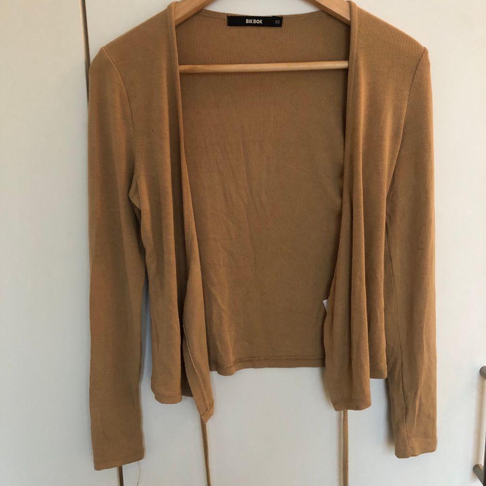 En mörkbeige tröja med snören som man knyter runt midjan. Köpt från bikbok i stl xs men passar även s. I gott skick och passar perfekt till allt. Toppar.