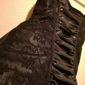 Svart linne med partier i spets på sidorna och glansigt veckat material i mitten. Justerbara axelband. Använd enstaka gång.
