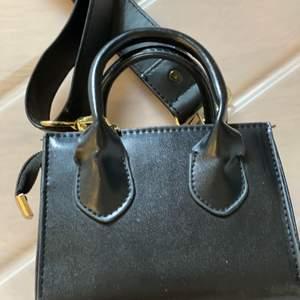 En svart liten fashion väska med tjockt bälte. Budgivning startar vid 350kr