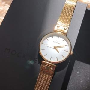 """Säljer min fina klocka i """"guld"""" från Mockberg. Fint skick! Modell: Livia no.38. Orginalbox finns. Säljer pga köp av en likadan med mindre ur. Nypris 1799kr. Pris kan diskuteras vid snabb affär. Kan mötas i Stockholm alt. Köparen står för frakt."""