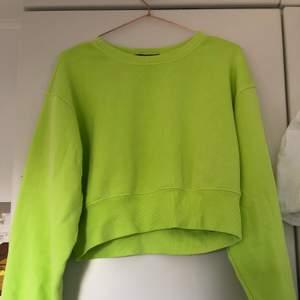 En neon grön sweatshirt som är croppad. Den är ganska kort men det beror helt på vilken storlek man är. Den är köpt i New York. Frakt tillkommer. Priset är förhandlingsbart.