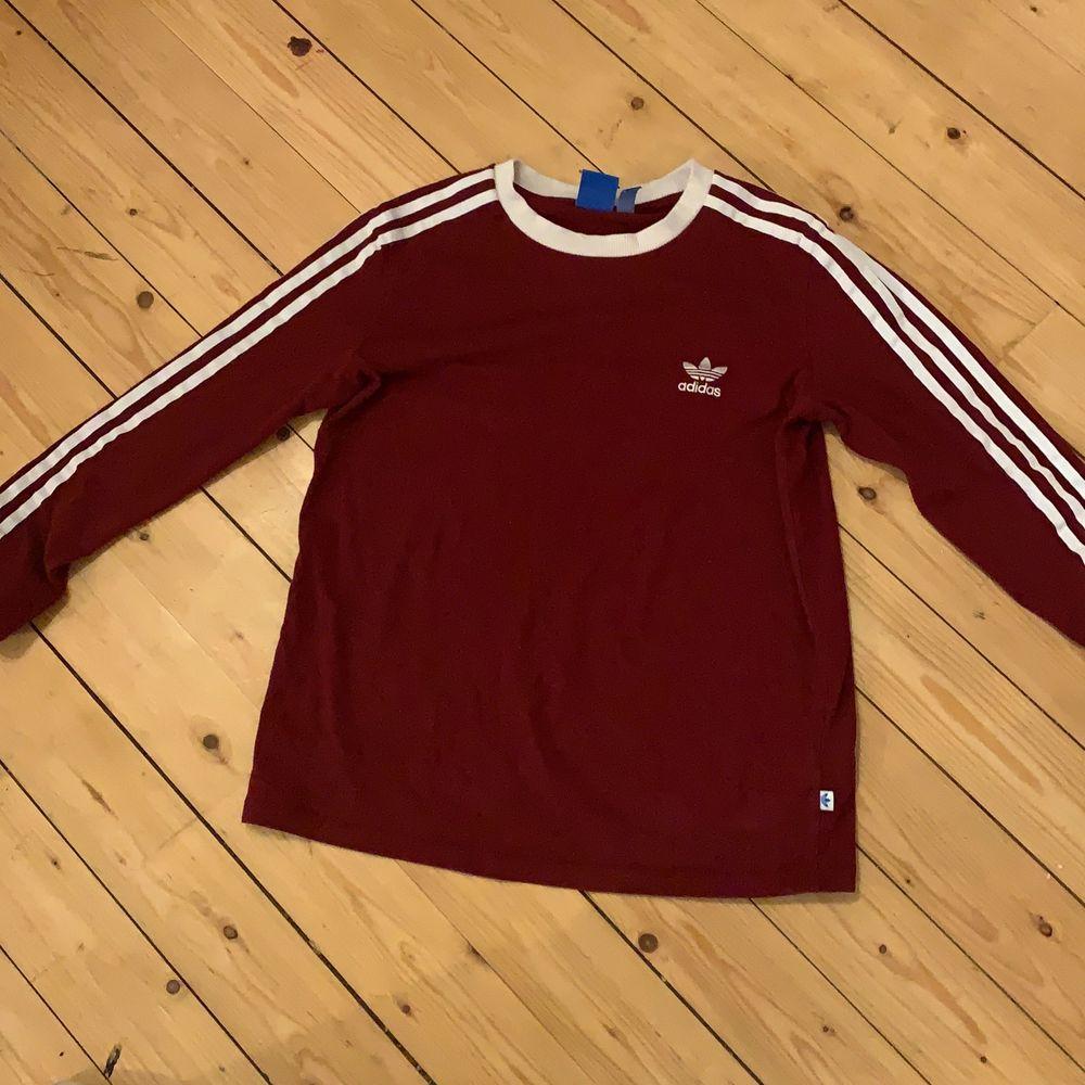 Vinröd adidas tröja med litet tryck på bröstets och ränder på armarna i storlek liten M. Tröjor & Koftor.