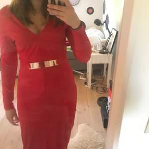 En röd klänning med slits i fram och guld bricka vid midjan. Aldrig använd👍🏼. Köpt på hm i Jordanien 🇯🇴 passar dig i storlek M!❤️