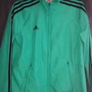 Adidas tröja med dragkedja i träningsmaterial men snygg till vardags också, den är i storlek 36 (S).