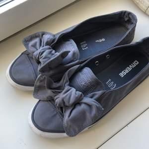 Ett par söta Converse sandaler med stora rosetter längst fram. Suuuuper bekväma och sköna! Äkta Converse! Skulle beskriva som blå-gråa, lite blandning. De är i storlek 40 men är små i storleken så passade för 38,5/39.Skriv vid intresse! :) (lämnar i stan)
