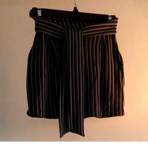 Green, black and khaki striped mini skirt with front tie and pockets. Stretch material in the back. From Pull & Bear