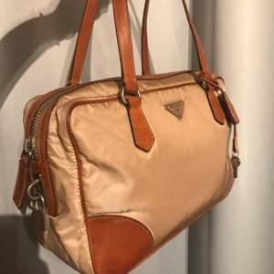 Äkta Prada vintage Baguette Nylon/canvas leatherhand bag.Det finns en nyckel för att låsa väskanär.mått B 28H18cm. Frakt: PostNord spårbart paket 63 kr. Betalning: Swish/Kort