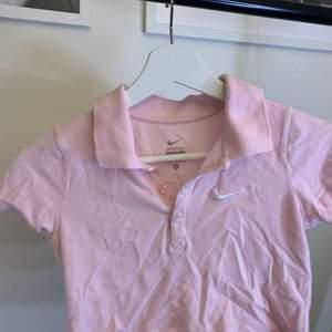 En ljusrosa piké tröja som jag klippt av så den är kort.