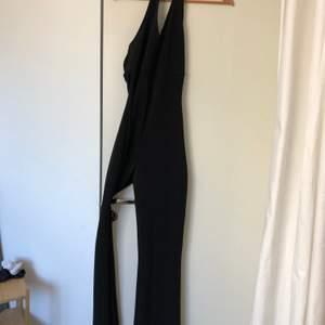En festlig svart jumpsuit med öppen rygg. Köpt på Beyond retro använd en gång på nyår. En riktig festlig dräkt