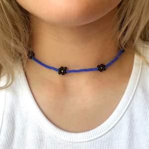 Pärlhalsband med blåa pärlor och svarta blommor. Töjbar tråd och bra kvalitet. 11 kr frakt💕