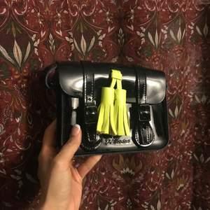 Helt oanvänd handväska i lack. Får plats med telefon och plånbok o ett läppglans typ.