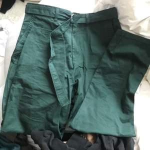 Chinosmaterial. Fin grön färg. Korta i benen. Passar typ XS/S. Snyggt bälte att tighta till med.