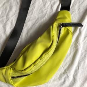 En grön/gul väska, använd fåtal gånger. Det är några svarta små fläckar på som man ser på bilderna. Annars är den i bra skick.