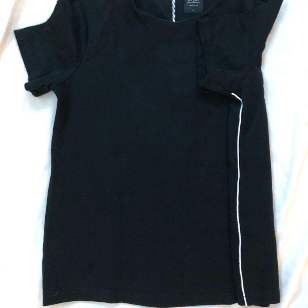 T-Shirt från ONLY i väldigt stretchigt material. Med vita sträck längst med sidorna. Med dragkedja 15 cm längst med ryggen från nacken.. T-shirts.