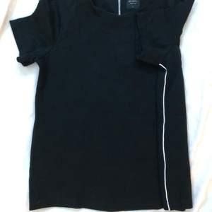 T-Shirt från ONLY i väldigt stretchigt material. Med vita sträck längst med sidorna. Med dragkedja 15 cm längst med ryggen från nacken.