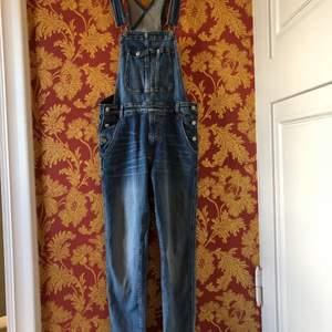 Plagget är köpt för ett tag sedan men endast använd en gång. Längden på hängslena är justerbara. Finns även knappar och fickor på sidorna. Materialet är jeans.