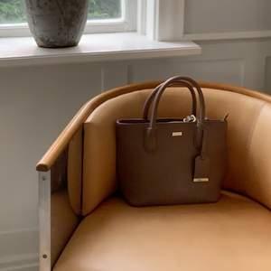 säljer min fina väska ifrån donna donna i en lilla, brun nude färg , använd en gång och har annars endast stått på en hylla . perfekt skick & tillkommer axelband . ordpris är 500 kronor .