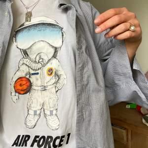 """Nike t-shirt med """"airforce one"""" tryck. Fina detaljer, som att austronauten har en basketboll med Nike-märket på. Borde matchas med air force 1-skorna! Är i strlk S och från killavdelningen så passar XS/S och M."""