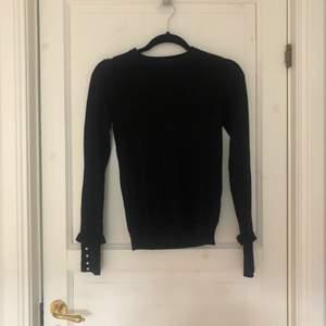 Långärmad svart tröja från zara med volang och pärlor vid muddarna. Mjukt och lite tjockare material. Sitter relativt tight och passar till allt.