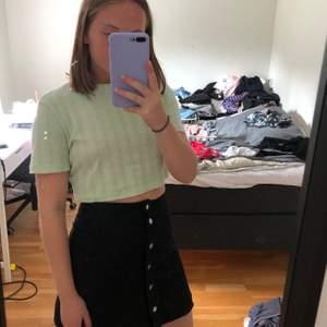 En svart kort kjol med knappar, sitter som en smäck!! Säljer då jag knappt använt