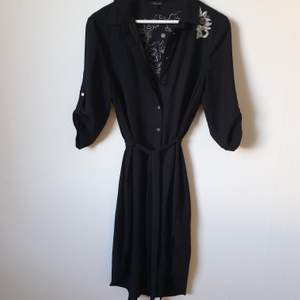 Black shirt dress wirh embroidery on the back . Size 12 - 38.