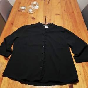 Svart skjorta med liten ståkrage i strl 44 från Jaqueline de young. Lös passform. Använd endast en gång.