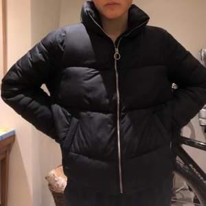 Svart  puffer-jacket från hollister med 100% återvunnen polyester! Den sitter jättesnyggt oversized på och är varm och skön till hösten/vintern. Den har två stora fickor som går att stänga med knapp och snören om man vill göra den tajtare runt midjan. Köpt förra hösten för ca 1000kr.