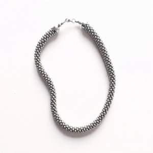 Oanvänt halsband i silverfärg.