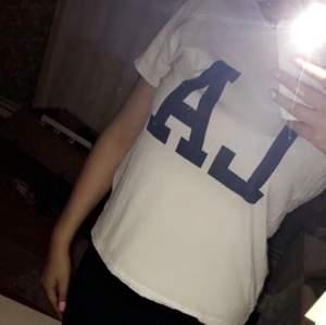 En vanlig vit T-shirt som det står LA på med blåa bokstäver.