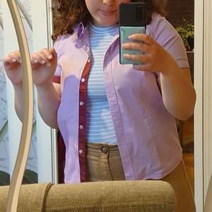 Super super fin unik pastell skjorta i lila färg . Köpt i en butik i Vackra Brasilien! Märket är Versani, storlek XS/S. Har röda  detaljer på ärmarna och på kragen med vita som prickar, vilket jag tycker är super gulligt med lila färgen.