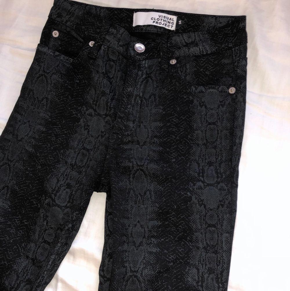 Oanvända svarta jeans med ormskinn tryck. Storlek 34. Lite tajtare vid midjan o lösare från knäna och neråt. Säljer pga lite för små i midjan. . Jeans & Byxor.